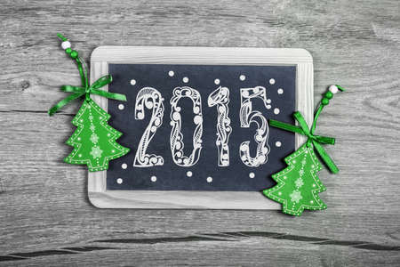 trinkets: Happy New Year 2015! Blackboard with caption 2015 on wooden surface decorated with green wooden trinkets.