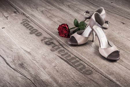 milonga: Argentine tango shoes and a rose on a wooden floor, caption Tango argentino
