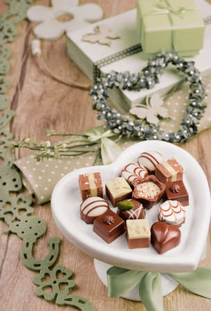 Spring arrangement with chocolate pralines, green objects and twigs photo