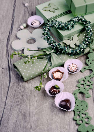 Green spring arrangement with chocolate pralines, toned image photo