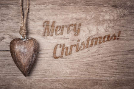 caption: Wooden heart decoration on vintage oak with burned caption Merry Christmas Stock Photo