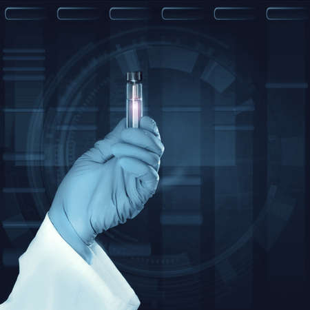nitril: Gloved hand holds a liquid sample in plastic tube in front of dark scientific