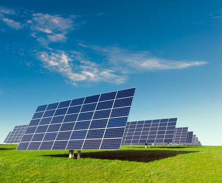 Solar panels on a field under blue sky photo