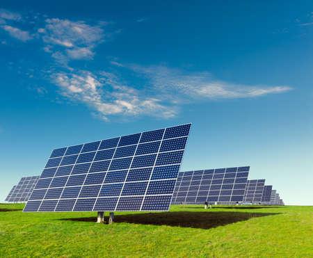 Solar panels on a field under blue sky photo