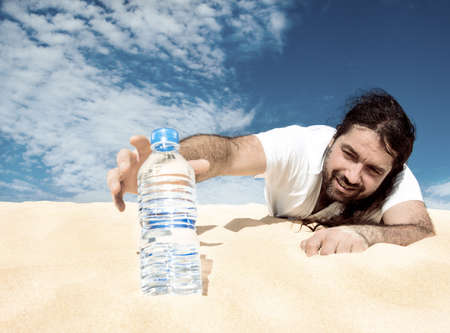 Thirsty man in the desert reaches for a bottle of water, toned image
