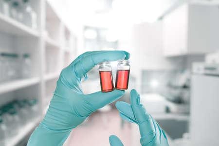 Twee handen in nitril handschoenen houden rode vloeistof monsters in wegwerp plastic flesjes, laboratorium interieur onscherp
