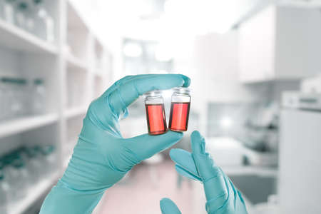 Two hands in nitril gloves hold red liquid samples in disposable plastic vials, laboratory interior out of focus