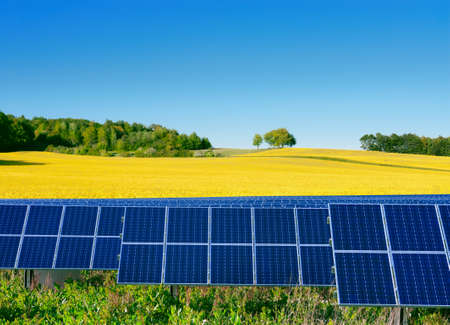 Solar power cells, rapeseed field and a bright blue sky Stock Photo