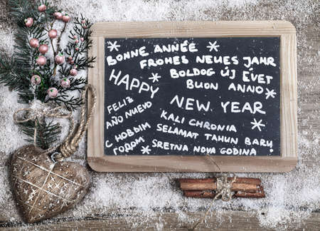 Happy new year in different languages written on a chalkboard with winter decorations photo