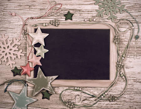 Black chalkboard with various winter decorations, text space photo
