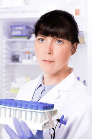 technical assistant: Serious clinitian, nurse or technical assistant takes samples out of the fridge Stock Photo
