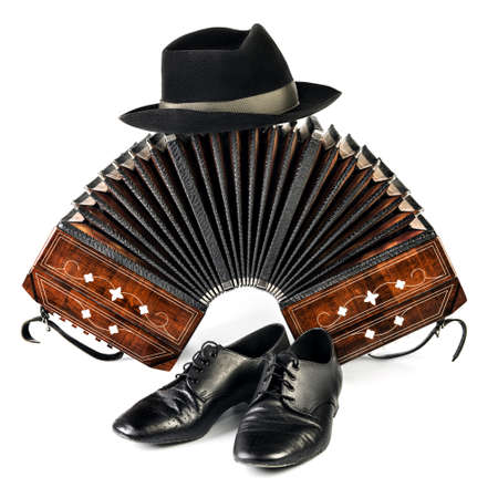milonga: Bandoneon, pair of tango shoes and a black hat on white  background Stock Photo