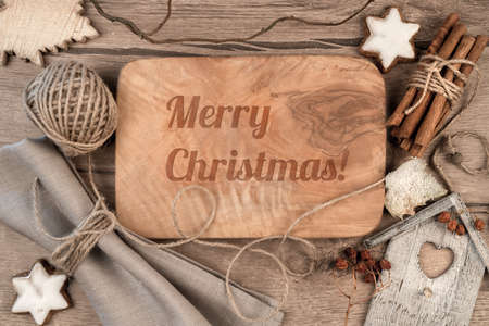 wooden table top view: Greeting card Merry Christmas burnt on wooden board with winter decorations around Stock Photo