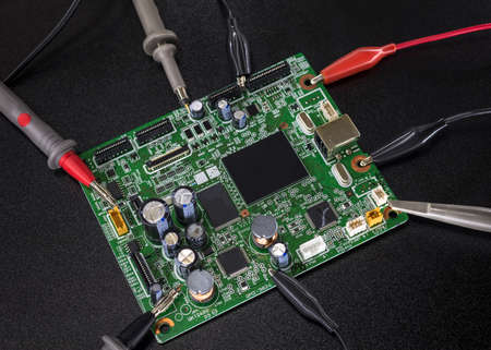 electronics equipment: Close-up of electronic circuit board with several microchips with tools and wires around Stock Photo