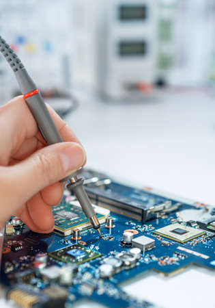 capacitor: Electronics repair service, hand of female tech fixes an electronic circuit, text space