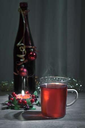 vin chaud: Vin chaud dans une tasse de verre, bouteille d�cor�e et bougie allum�e. Espace de texte