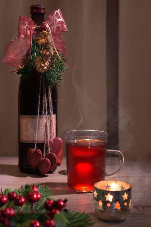 vin chaud: Vin chaud dans une tasse en verre, bouteille d�cor�e et bougie allum�e Banque d'images