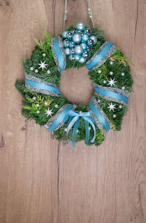 Christmas wreath on wooden door, space for your text photo