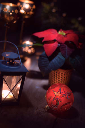 christmas flower: Poinsettia, red Christmas flower, bauble, candles and lantern on wooden table
