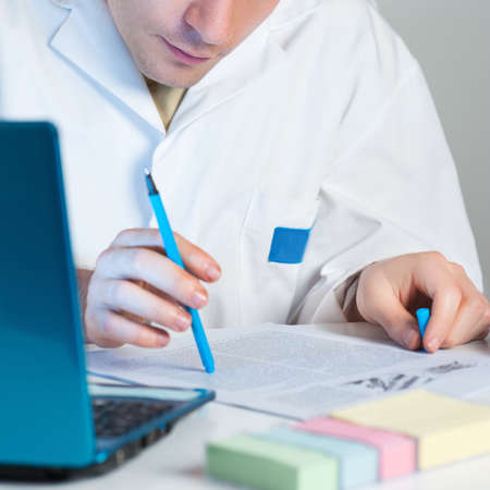 article writing: Young scientist reads an interesting research publication Stock Photo