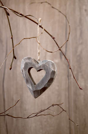 heavy heart: Heavy wooden heart hanging on dry twigs on wood. Happy Valentine!