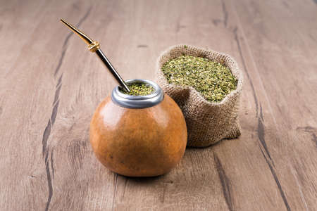 Yerba mate in a traditional calabash gourd and bag of dry herb 스톡 콘텐츠