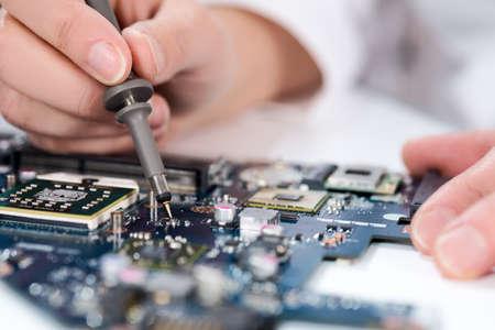 circuitos electronicos: Tecnológico de fondo con el primer probador en la comprobación de la placa base. Imagen borrosa de su texto en la parte superior. DOF superficial, foco exacto en la punta del probador