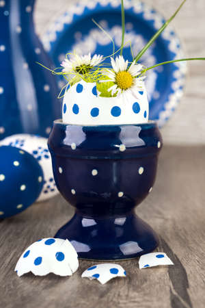 Blue ceramic Egg holder with flowers in egg shell and matching ceramics on wooden table. Happy Easter! photo