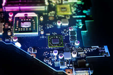 electronics parts: Microchips on a circuit board on dark background