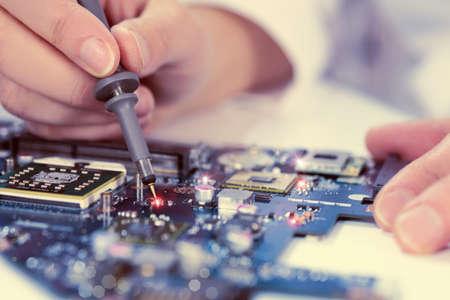 electricista: Tecnol�gico de fondo con el primer probador en la comprobaci�n de la placa base. Imagen de tonos. DOF superficial, foco exacto en la punta del probador