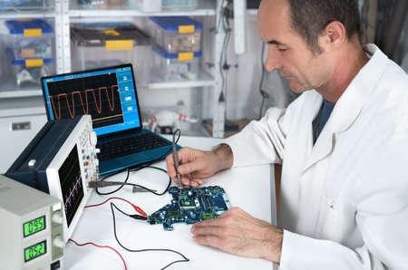 electricista: Obras tecnolog�a sexo masculino mayor en taller de reparaci�n de hardware Foto de archivo
