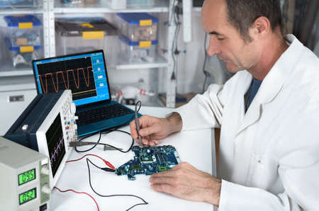 electronics: Senior male tech works in hardware repair facility