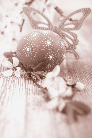 ornated: Blue ornated Easter Egg and a butterfly next to a twig with cherry flowers, sepia toning, text space