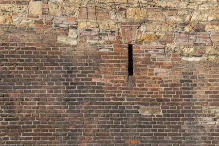 backround: Old brick wall with wild stone on tope and a narrow porthole, background image