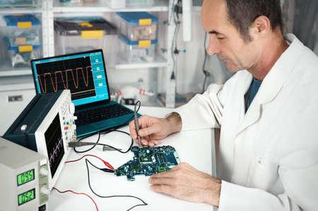 hardware repair: Senior male tech works in hardware repair facility