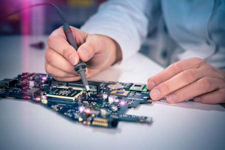 circuitos electricos: Correcciones Tech placa en su centro de servicio. Shallow DOF, se centran en las manos, la imagen es entonada con efectos de luz adicionales Foto de archivo