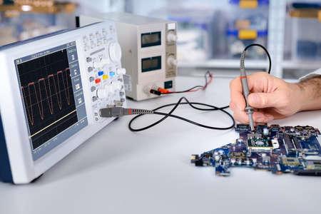 trabajando en computadora: Correcciones Tech placa en su centro de servicio. DOF bajo, foco en la mano, parte de moherboard y parte delantera del osciloscopio.