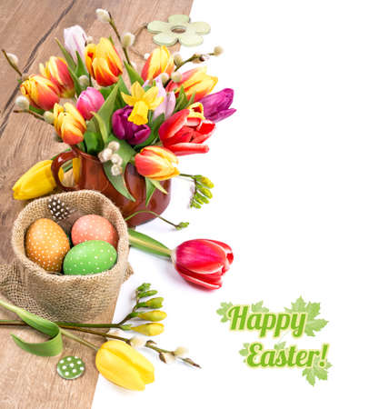 Colorful Easter border with bunch of tulips and Easter eggs on wood, white background, deep DOF, space for your text