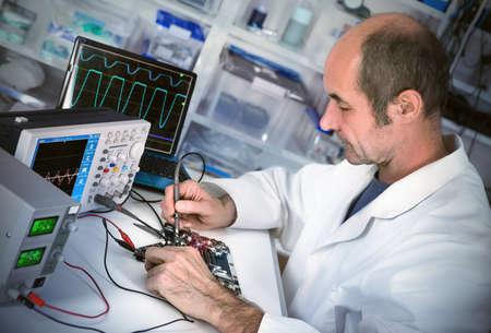 Senor corrections de technologie masculins carte mère sous un atelier de réparation d'ordinateur. Image teintée, shallow DOF, point sur le visage du travailleur.