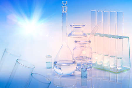 liquid level: Scientific background with chemical glass, flask and tubes. This is a background element with majority of frame out of focus. Focus is on small glass vial and round flask above the liquid level. Space for your text or caption. Stock Photo