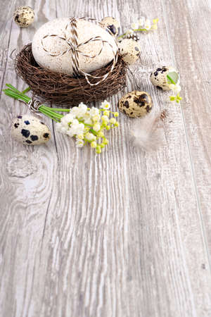 easter background: Easter background with natural eggs and lily of the valley flowers on wooden table, space for your text Stock Photo