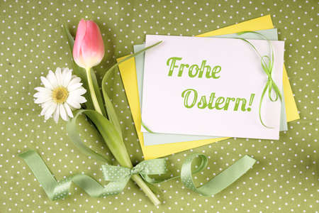 Ostern: Greeting card with caption Frohe Ostern (Happy Easter in  German) with flowers and ribbons