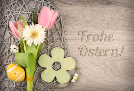 Ostern: Easter arragement with flowers and eggs on wood with caption Frohe Ostern! (Happy Easter in German)