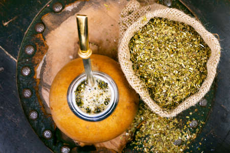 argentinean: Yerba mate in a traditional calabash gourd and bag of dry herb Stock Photo
