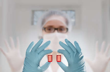 Two gloved hands hold red liquid samples in front of an eager tech out of focus. Concept image for vaccine development or new tests of biological or chemical samples. Space for your text photo