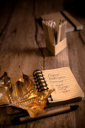 recipe decorated: Open notebook with cookie recipe on a table with pencils and decorated marple leaf. This image is toned. Shallow DOF, focus on the writing. Stock Photo
