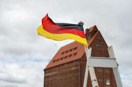 flaps: German flag flaps on the wind in historical harbor of Stralsund in Northern Germany Stock Photo