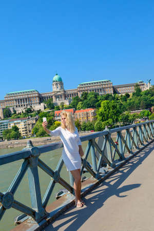 the chain bridge: Blonde tourist making selfie in front of Buda Castle on the famous Chain Bridge in Budapest. Focus on the girl Stock Photo