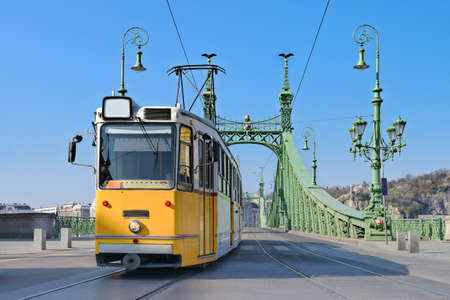 public transportation: Historic tram on Freedom Bridge in Budapest Hungary on a bright day