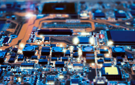 manufacture: Closeup on electronic board in hardware repair shop, blurred and toned image. Shallow DOF, focus on the middle left field